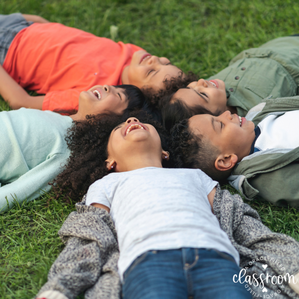 Five children are laying on the grass with their heads touching while looking up at the sky and laughing. Celebrating Earth Day with Kids