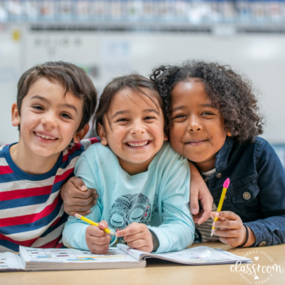 Three students in class smiling and doing classwork together